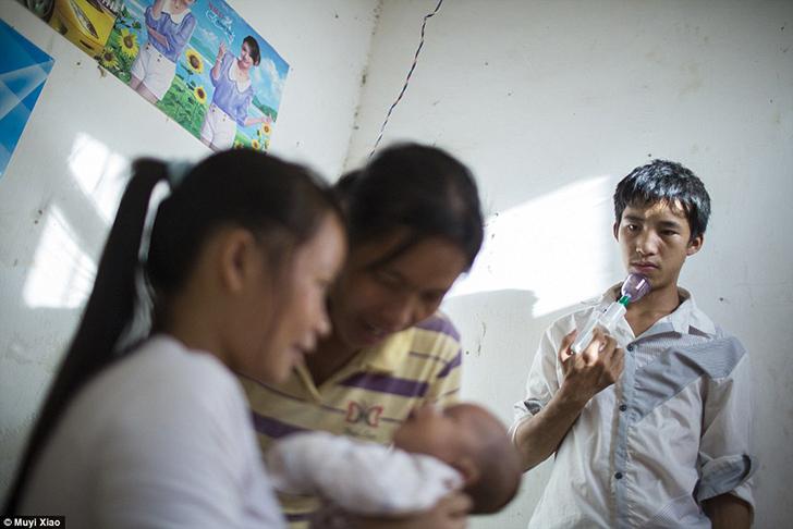 17-летний Сяо Мин держит молокоотсос, а его мать и 16-летняя жена держат сына.