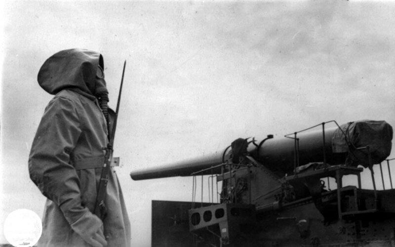 Краснофлотец в противогазе на посту у 10-дм (254-мм) пушки