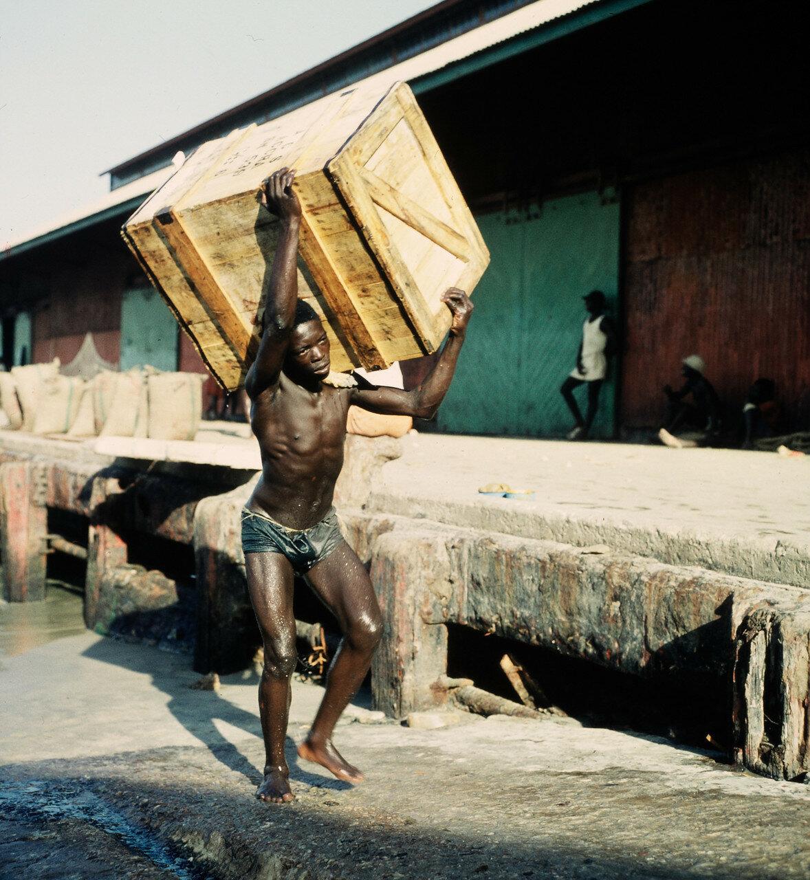 Носильщик переносит ящик из прибойных шлюпок на склад
