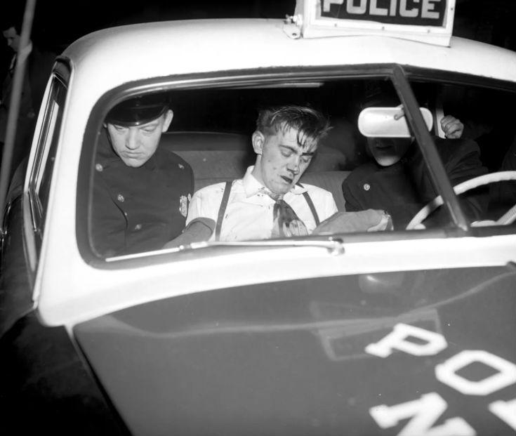Подозреваемый в стрельбе покидает с полицейскими больницу, 14 ноября 1949 года.