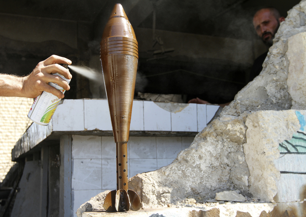 A Free Syrian Army fighter spray paints an improvised mortar shell in Aleppo