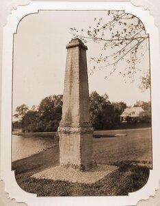 Вид обелиска, установленного в дворцовом парке у одного из прудов.