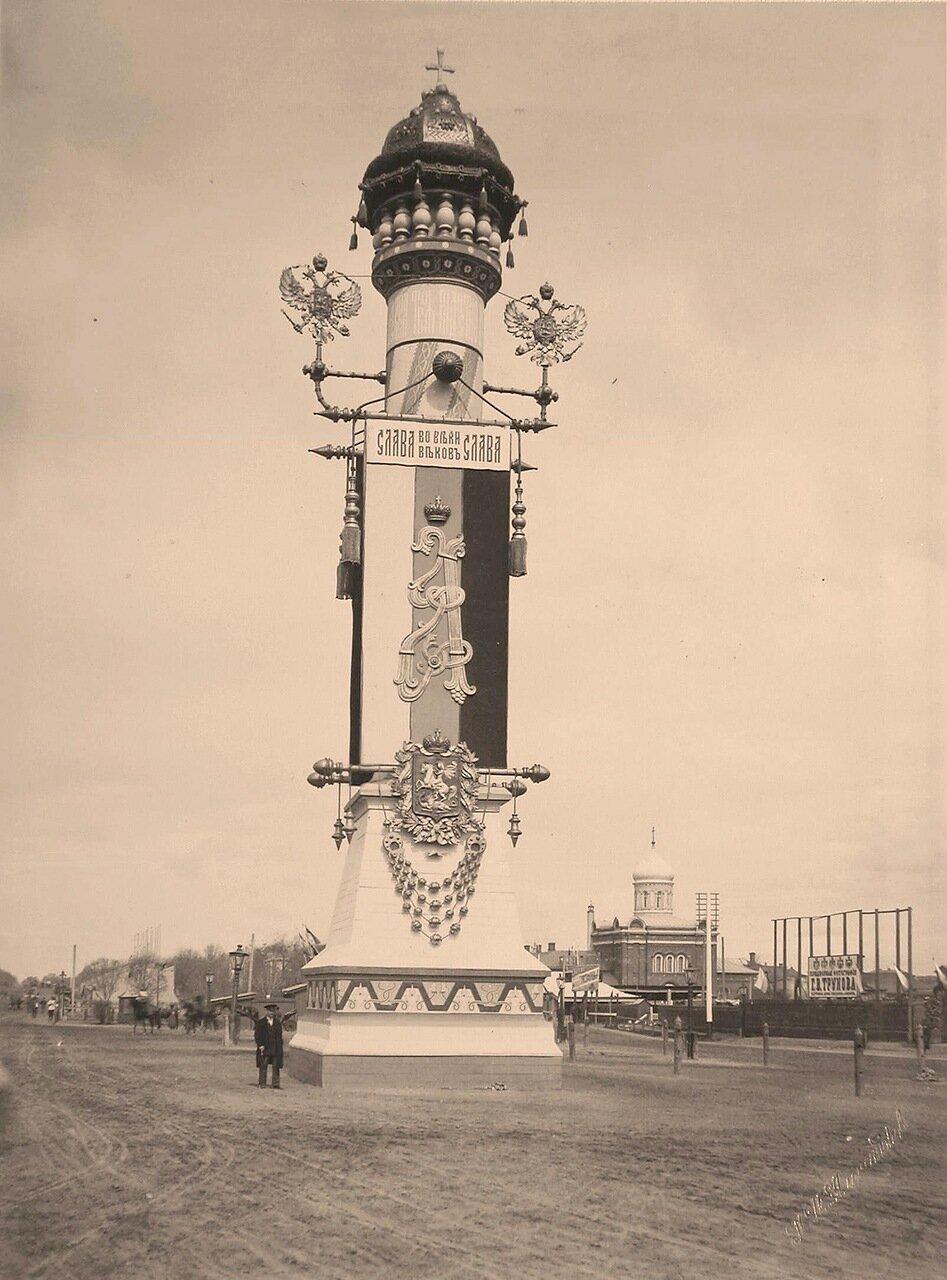 Вид одной из двух празднично украшенных и иллюминированных колонн, установленной к торжественной коронации на площади Тверской заставы перед Триумфальными воротами