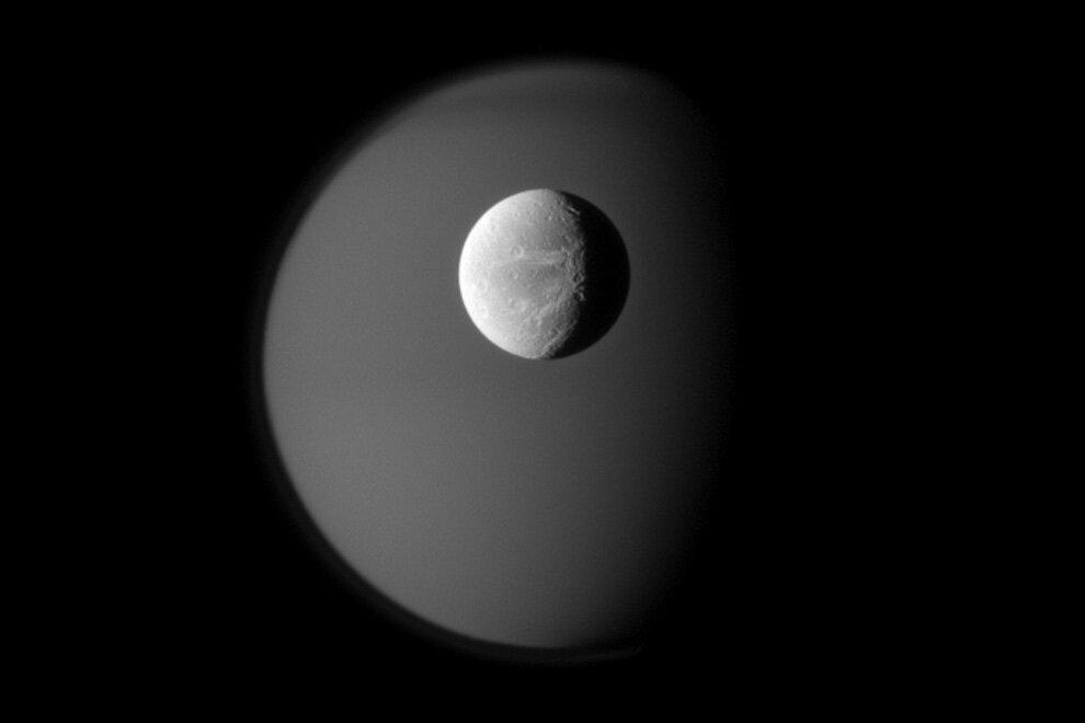 Поверхность спутника Сатурна Дионы на фоне туманного призрачного Титана