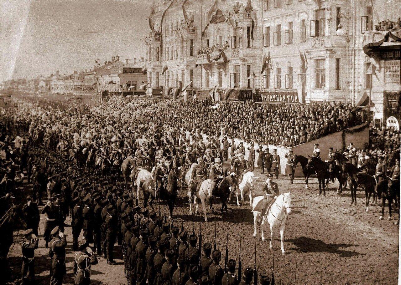 Император Николай II (на белом коне) в сопровождении свиты шествует перед трибунами от Триумфальных ворот по Тверской улице в  день торжественного въезда в Москву их императорских величеств