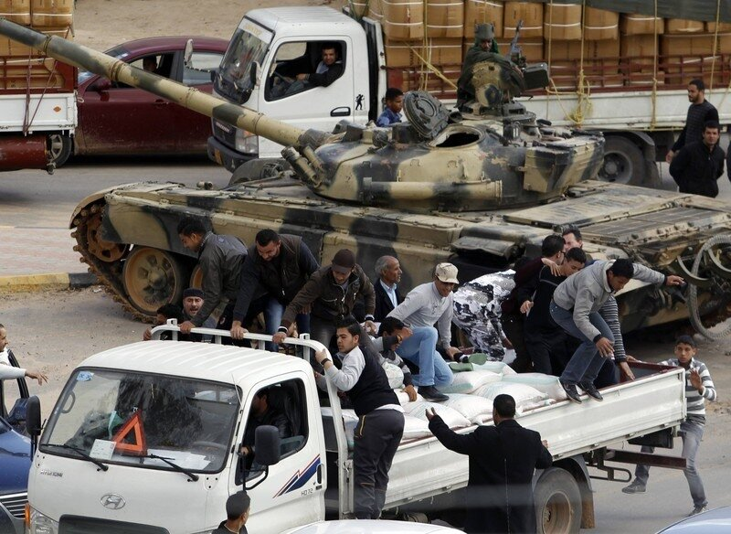 Men jump from a truck carrying flour, near a Libyan army tank guarding a traffic intersection in Tripoli