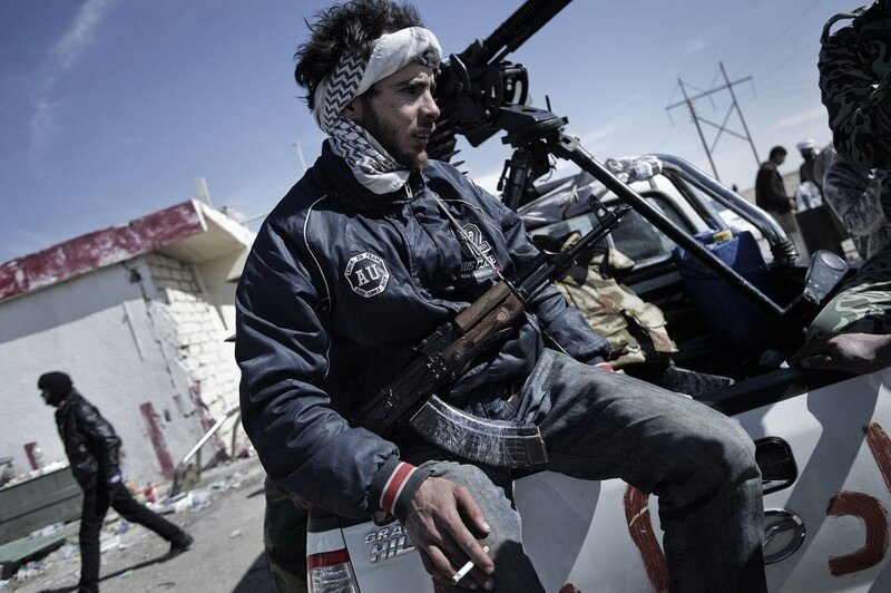 An anti Libyan government fighter sits o
