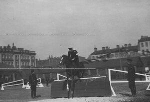 Офицер на лошади, берущий барьер во время конных состязаний.