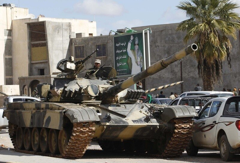 A Libyan army tank guards a traffic intersection near a mural adulating Libyan leader Gaddafi in Tripoli