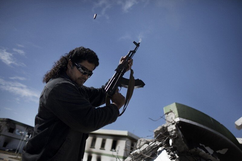 A Libyan armed man shoots in the air wit