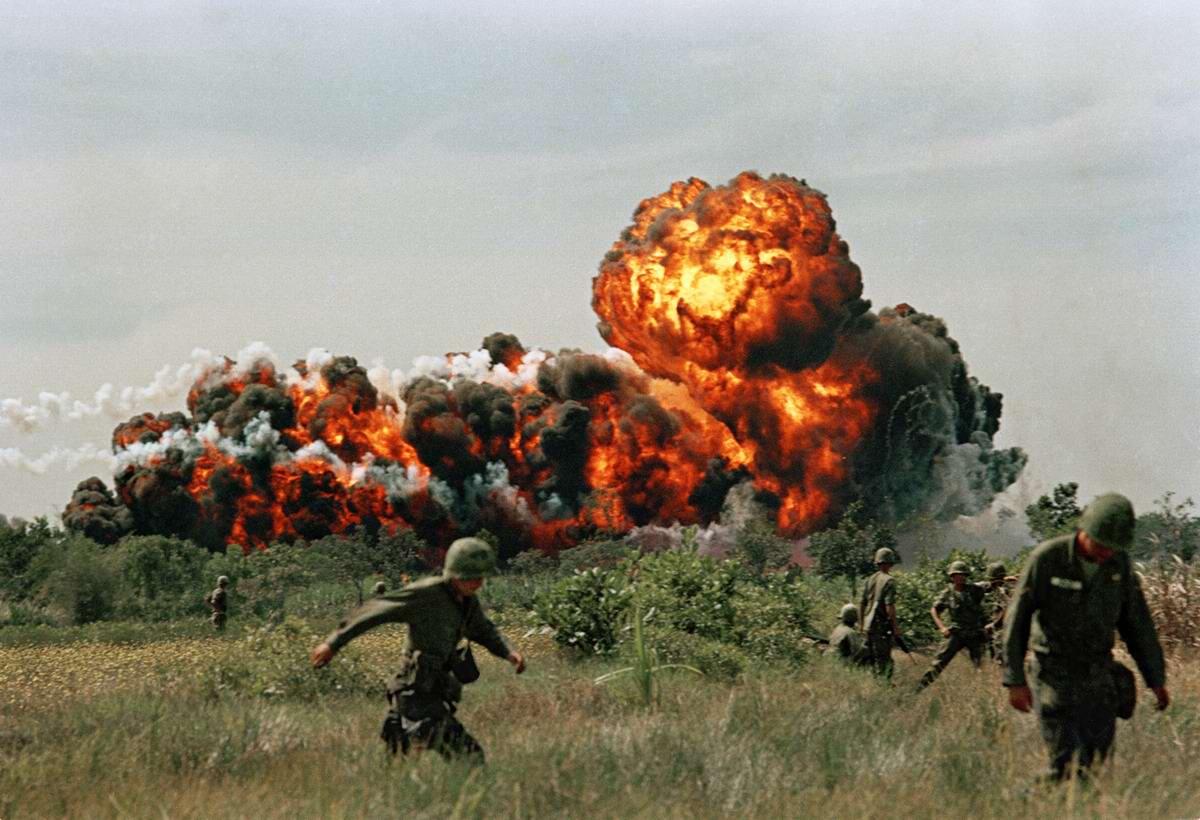 Огненные шары от взрывов напалма поблизости от расположения солдат американских войск
