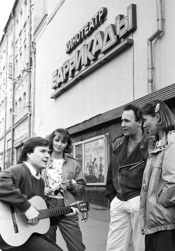 Композитор Григорий Гладков исполняет свои песни у кинотеатра мультипликационного фильма «Баррикады»