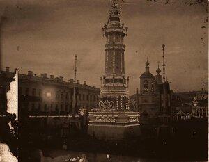 Вид одной из празднично украшенных и иллюминированных к торжествам коронации колонн (высотой 16 сажен), установленной в Охотном ряду напротив часовни Александра Невского.