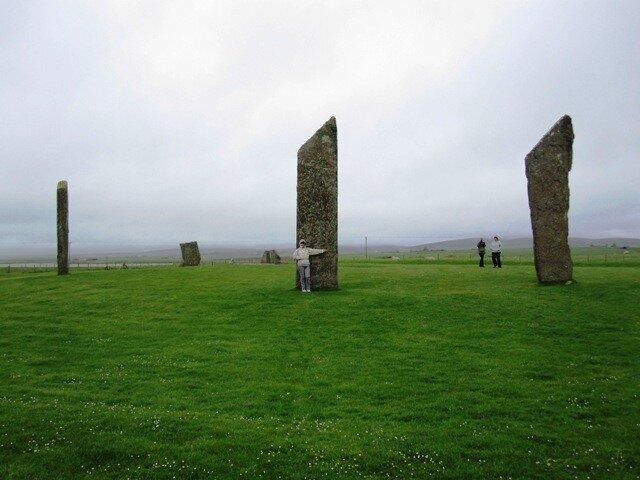 Прислонилась к стоящим камням Стеннесса на Оркнейских островах Шотландии
