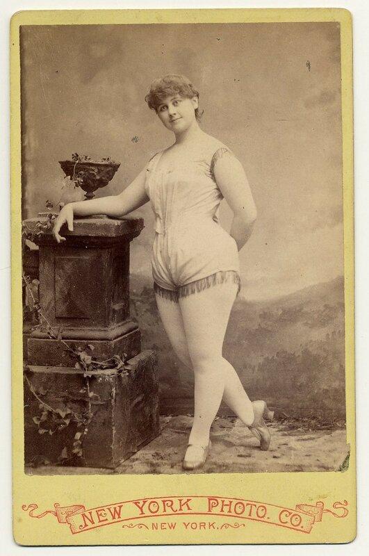 1890. Clara Davenport in short sleeveless costume fringed at legs and armholes.