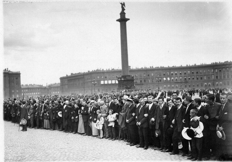 Манифестанты смотрят на проходящие колонны мобилизованных в армию.