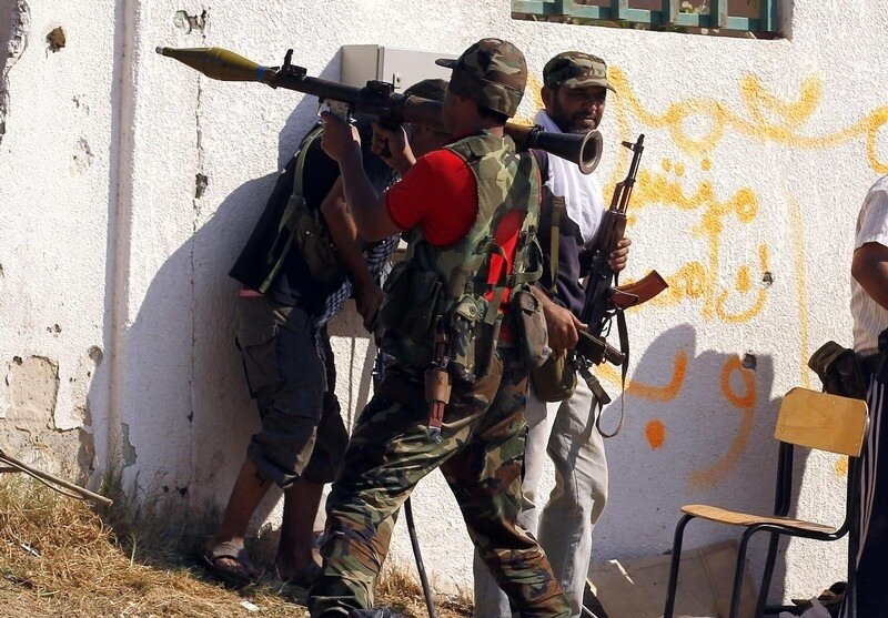 A Libyan rebel fighter prepares to fire an RPG towards a sniper position in Tripoli