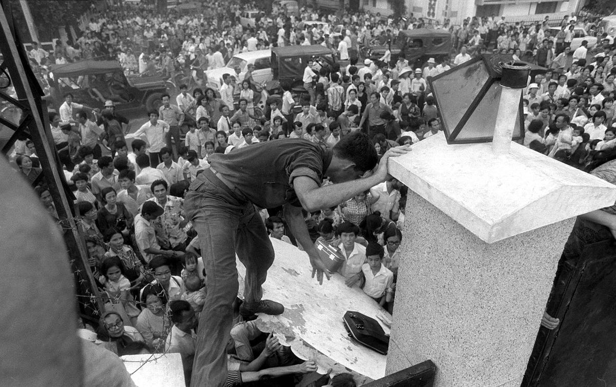 Паническое бегство: Жители Южного Вьетнама из числа сотрудничавших с местным режимом и американскими войсками штурмуют стену посольства США в Сайгоне, пытаясь достичь зоны эвакуации вертолетами после того, как последние американцы уже покинули территорию Вьетнама