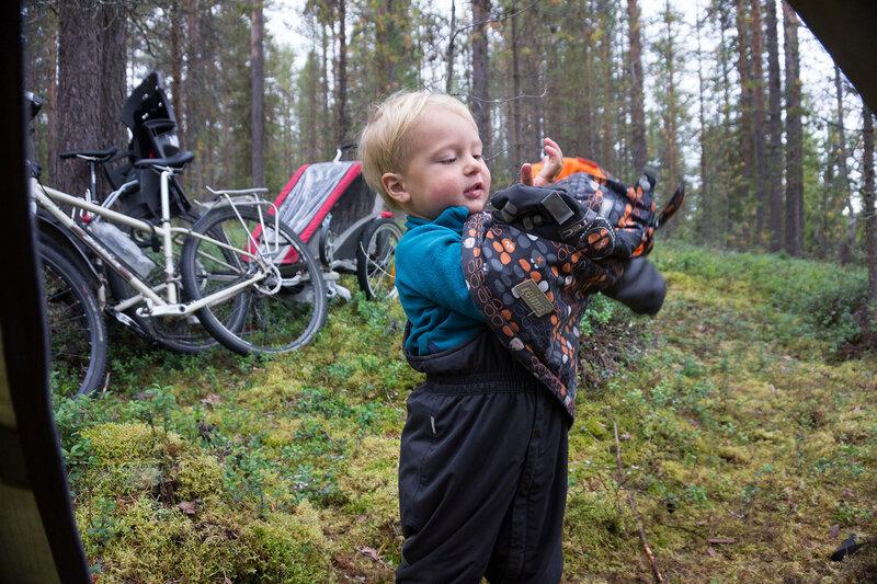 двухлетний ребенок пытается сам одеть куртку