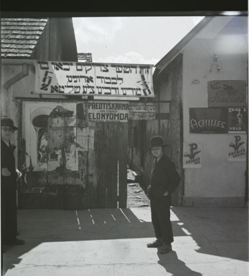 Мальчик стоит перед вывеской с надписью «Это врата через которые придут праведники»