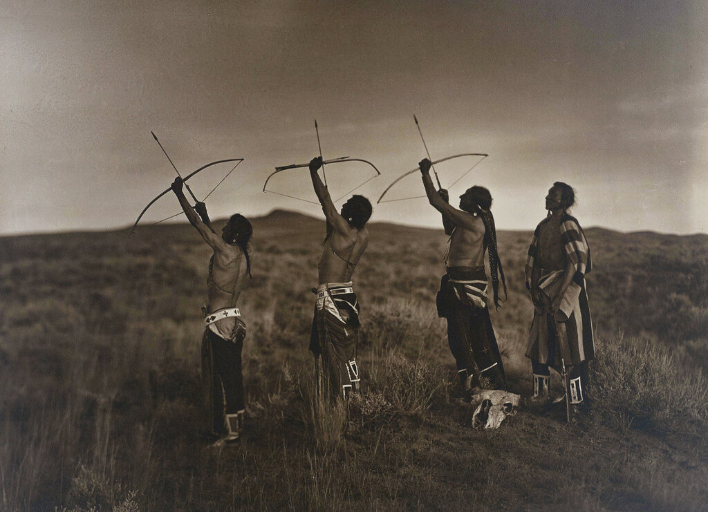Native American men aim bows and arrows into the sky probably in Big Horn County, Montana, between 1908 and 1913