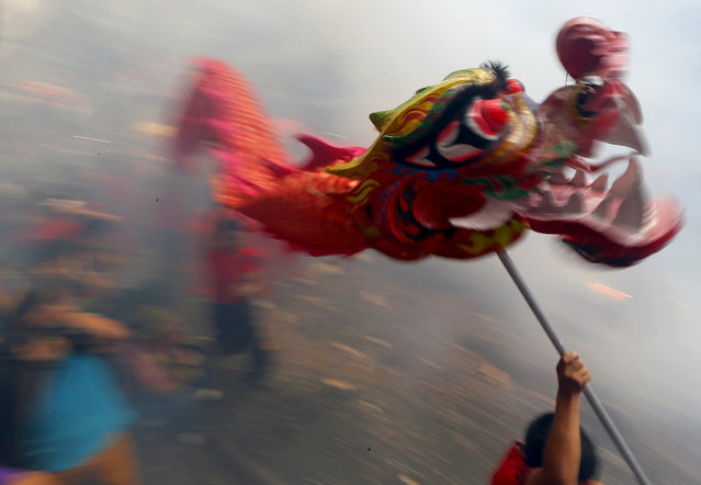 Dragon and lion dancers perform amidst exploding firecrackers in celebration of the Chinese Lunar Ne