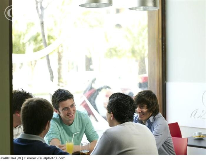 Group of teenage males talking in a cafe