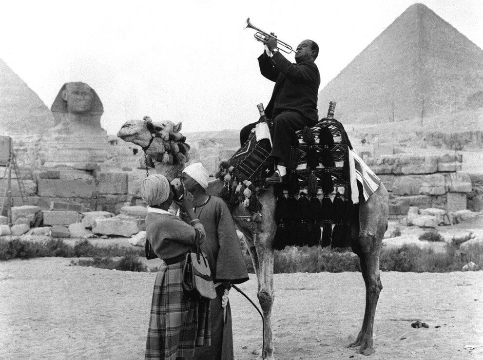 Луи  Армстронг верхом на верблюде, очаровывает древнего сфинкса и пирамиды в Гизе, недалеко от Каира, Египет, 28 января 1961 года. Жена Люсиль снимает его на видео