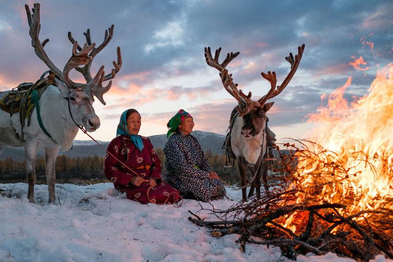 Женщины наслаждаются теплом от костра.