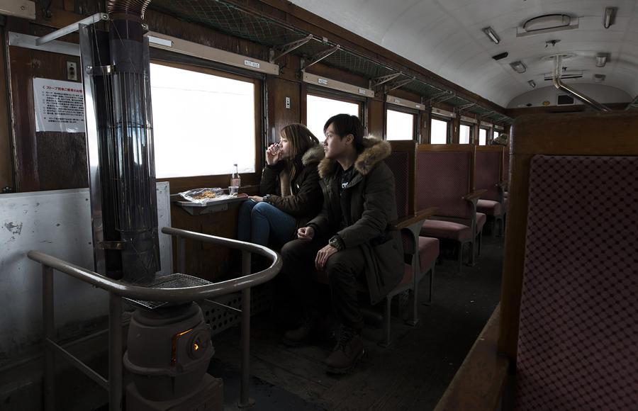 Пассажиры греются возле печки, 2 февраля 2017 года, путешествуя между Goshogawara и Nakazato.
