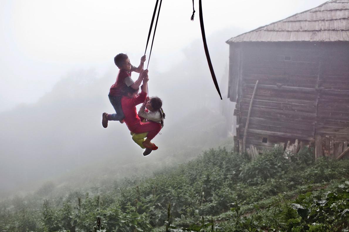 Дети катаются на веревке в туманный день. Для многих местных жителей детство быстро заканчивается из