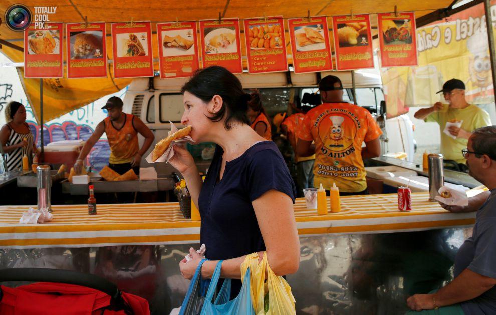 Люди перекусывают едой, купленной на уличном рынке в Рио-де-Жанейро, в том числе сладостями pastel d