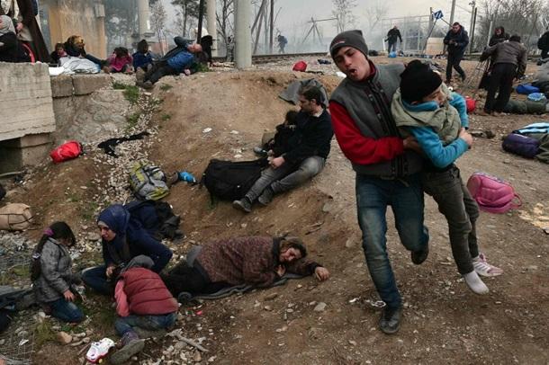 Беженцы в дождевиках в Греции