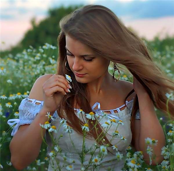 Русая девушка на ромашковом поле.