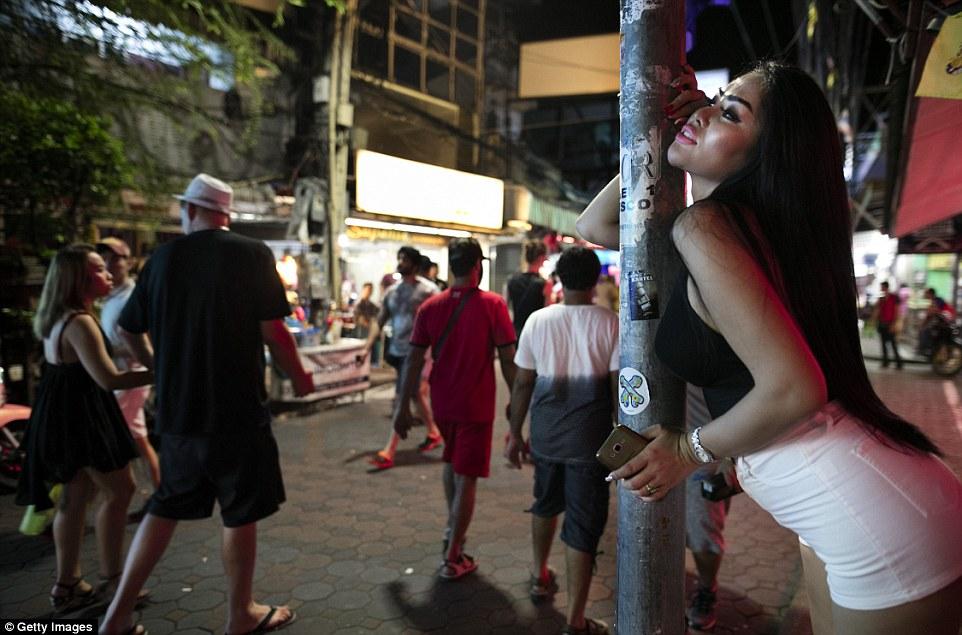 Девушка опирается на столб, принимая сексуальную позу.