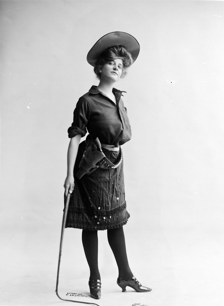 Studio portrait of a woman dressed as a cowgirl who stands with a whip in her hand. 1903.