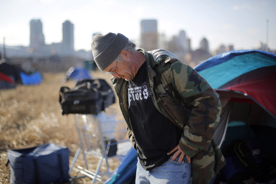 Terry, a homeless man who only gave his first name, stands outside his tent at a large homeless enca
