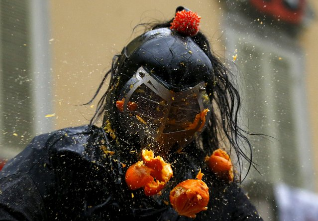A member of a rival team is hit by an orange during an annual carnival battle in the northern Italia