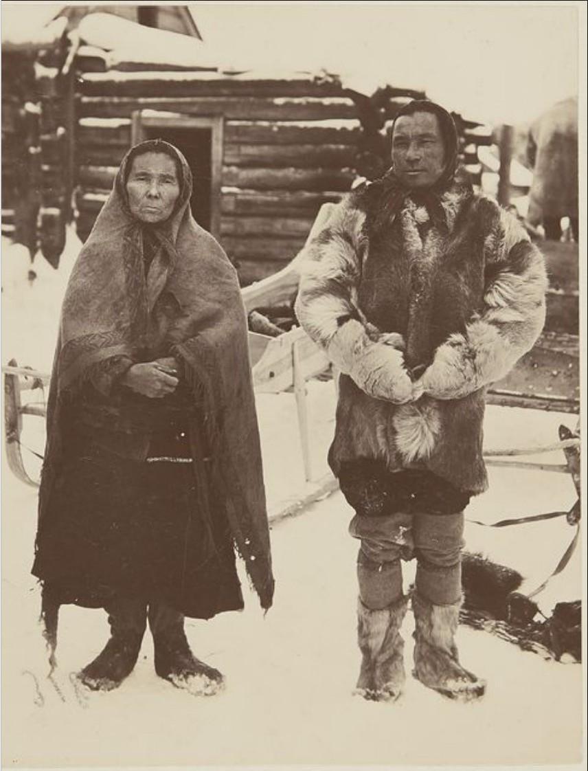 Супружеская пара хантов в зимних одеждах возле своего дома. Вах