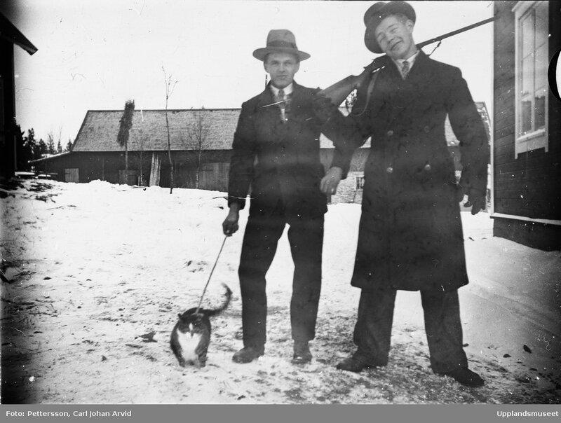 Tva man med gevar och katt i koppel, sannolikt Funbo socken, Uppland, 1910 - 1950, Fotograf Pettersson, Carl Johan Arvid.