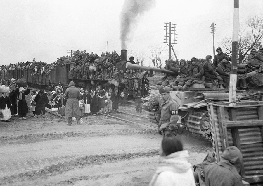 A trainload of refugees halts at a crossing near Osan, South Korea on January 15, 1951, as a British