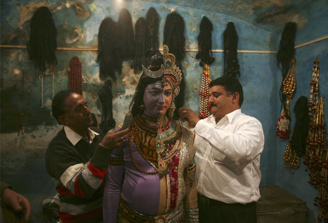 An artist is helped with getting dressed as both Hindu god Lord Shiva and his wife goddess Parvati b