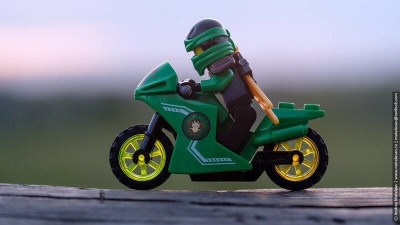 лего человечек едет на мотоцикле, на зеленом мотоцикле