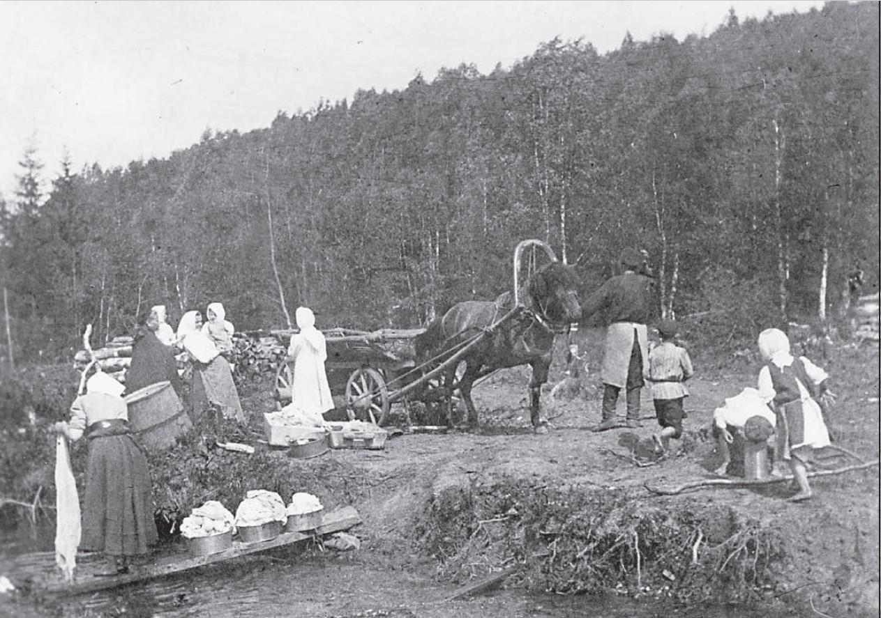 Члены Крестовоздвиженского православного трудового братства во время стирки белья в реке
