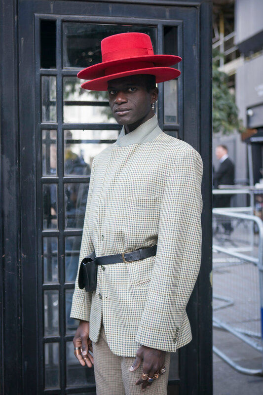 LONDON, ENGLAND - September 15, 2017 Beautiful and stylish man in red hat and elegant suit posing during the London Fashion Week. outside Eudon Choi