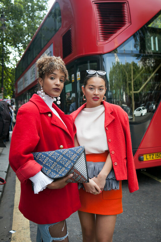 LONDON, ENGLAND - September 15, 2017 Beautiful and stylish woman in red coat and skirt posing during the London Fashion Week. outside Eudon Choi