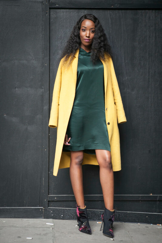 LONDON, ENGLAND - September 15, 2017 Beautiful and stylish woman in yellow coat and green dress posing during the London Fashion Week. outside Eudon Choi