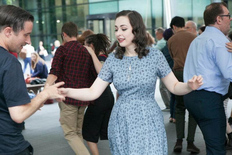 People are dancing lindy hop around the Spitalfelds market
