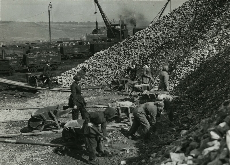 British women chemical workers in the Midlands taking limestone from stock, loading and wheeling barrows of lime to wagons