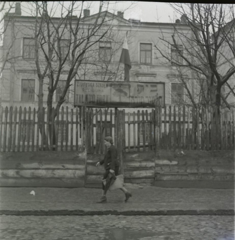 Женщина, идущая мимо Талмуд Тора (еврейская религиозная школа).